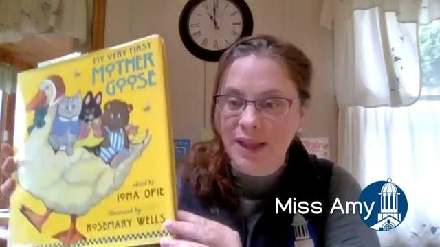 Miss Amy holds up the book My Very First Mother Goose