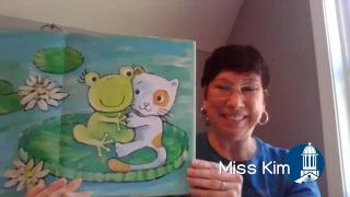 Miss Kim holding open a book that shows a frog and kitten